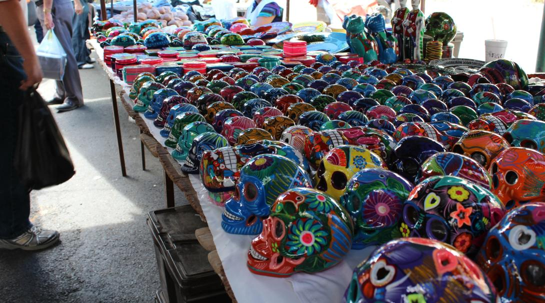 A street vendor in Mexico selling sugar skulls with many different colours and patterns on them